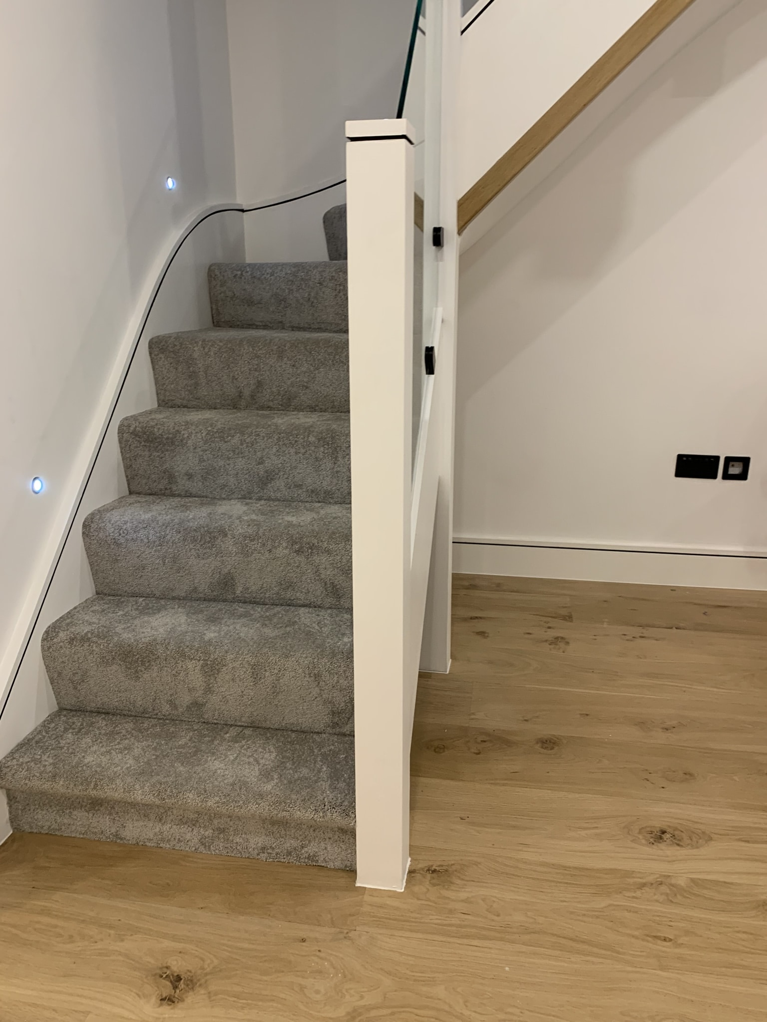 Staircase with carpet cover and toughened safety glass balustrade.