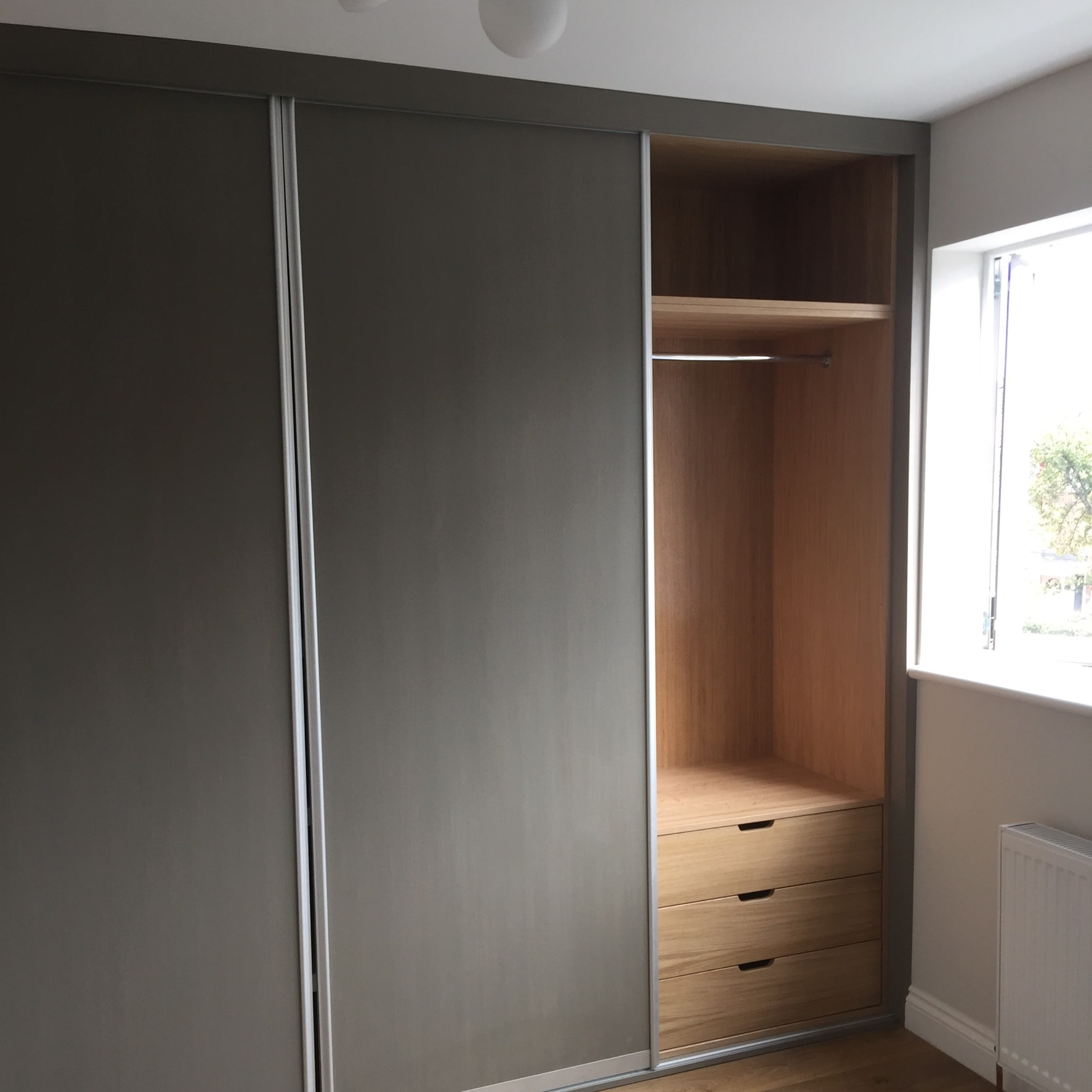 Built in wardrobe in grey with sliding door.