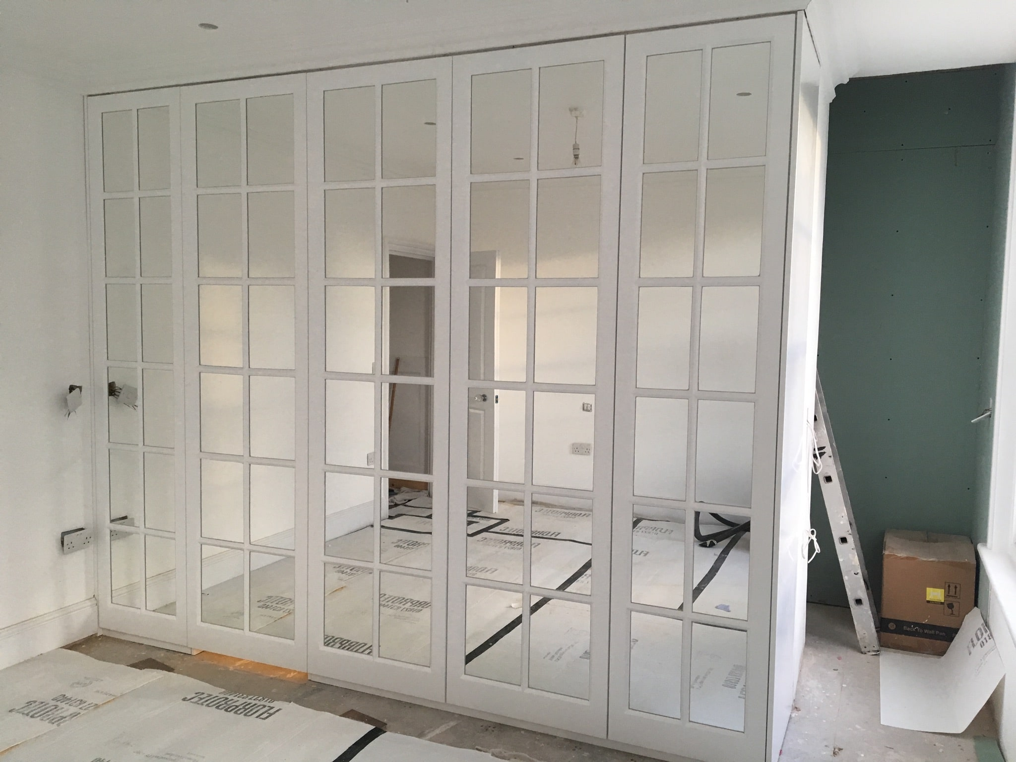 Fitted wardrobe with mirror door.
