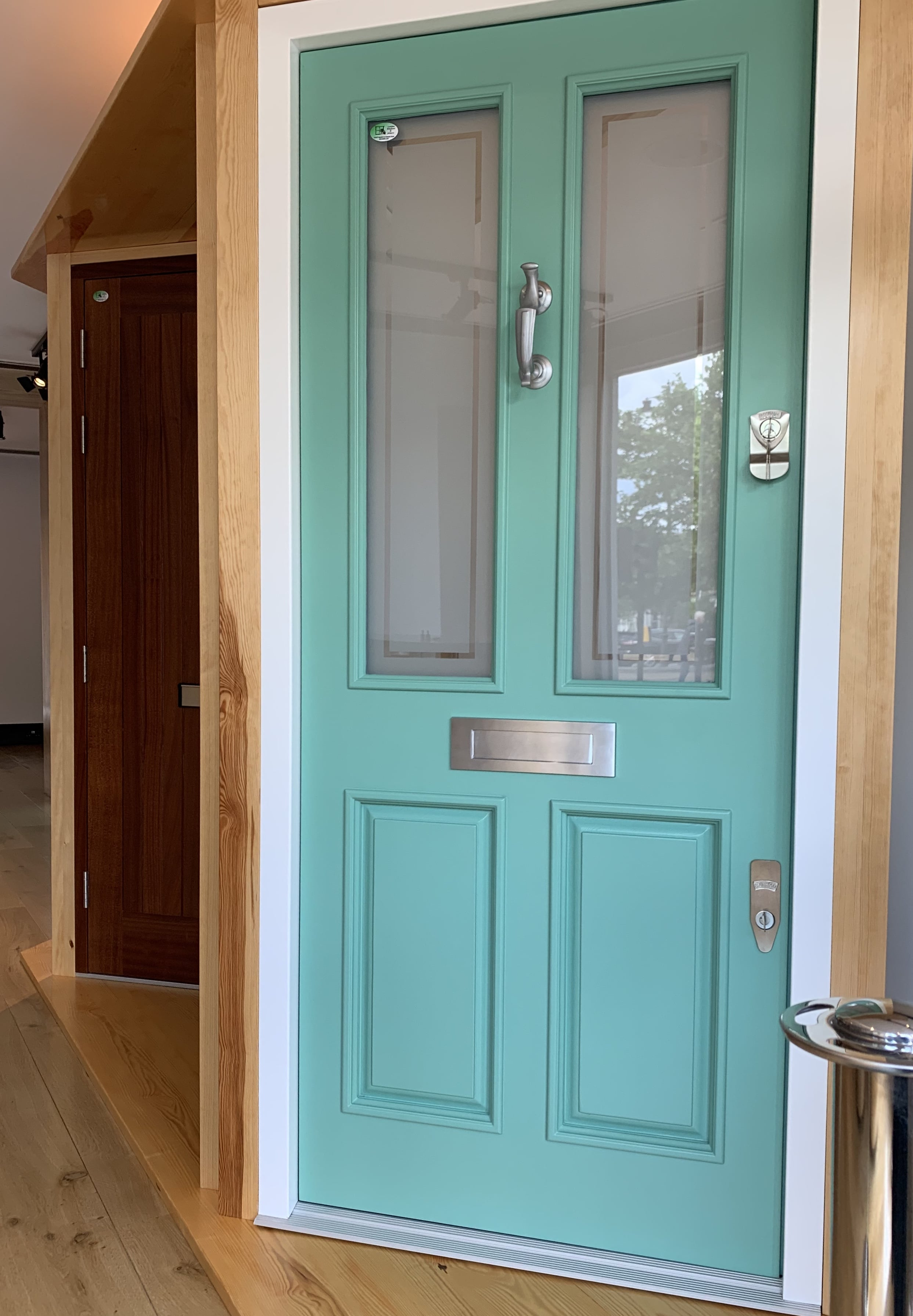 Four panel hardwood front door, featuring toughened decorative glass, door knocker and letter box. Banham double safety lock.