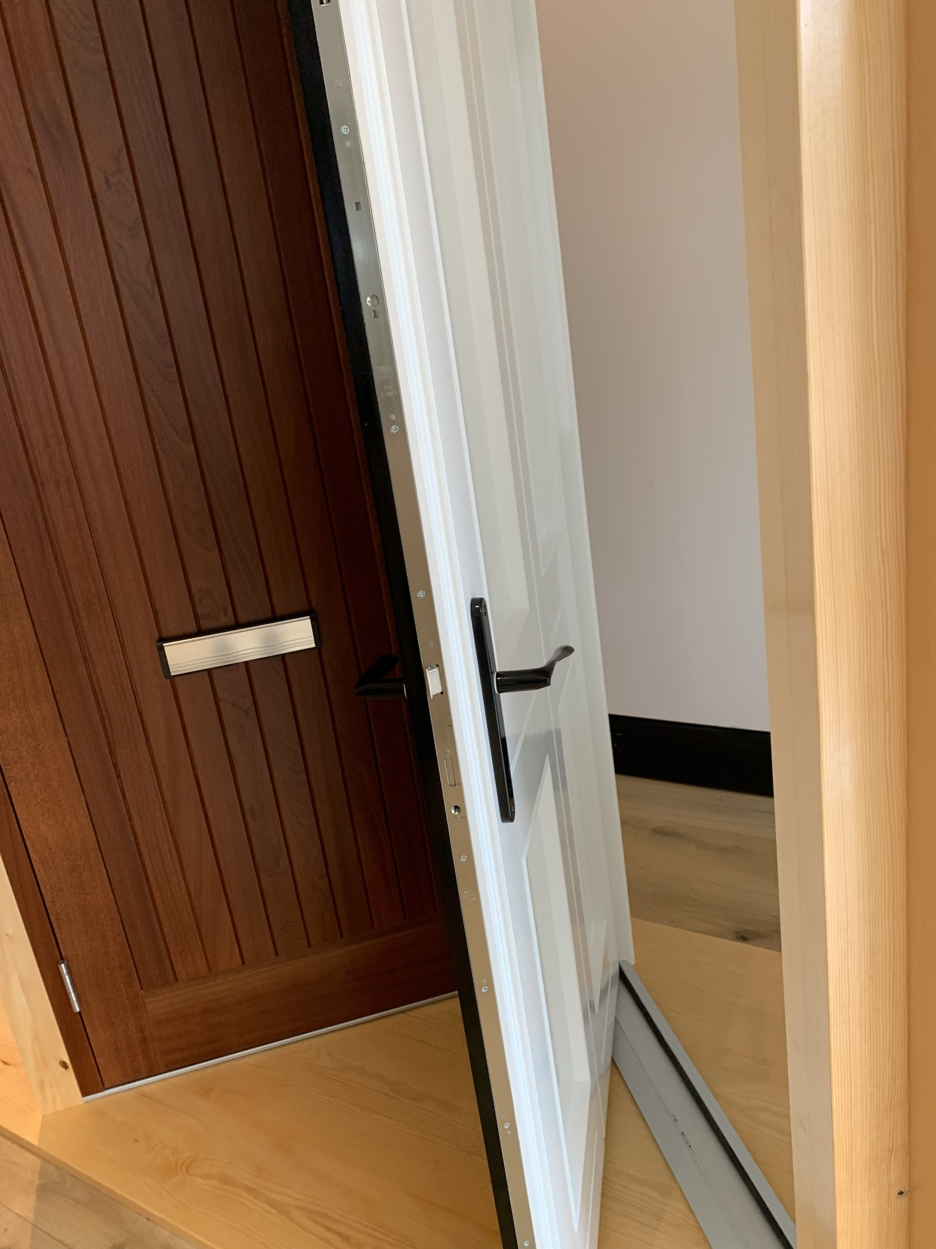 Four panel hardwood front door, factory fully finished in two colours - inside white and outside black. Multi point lock.