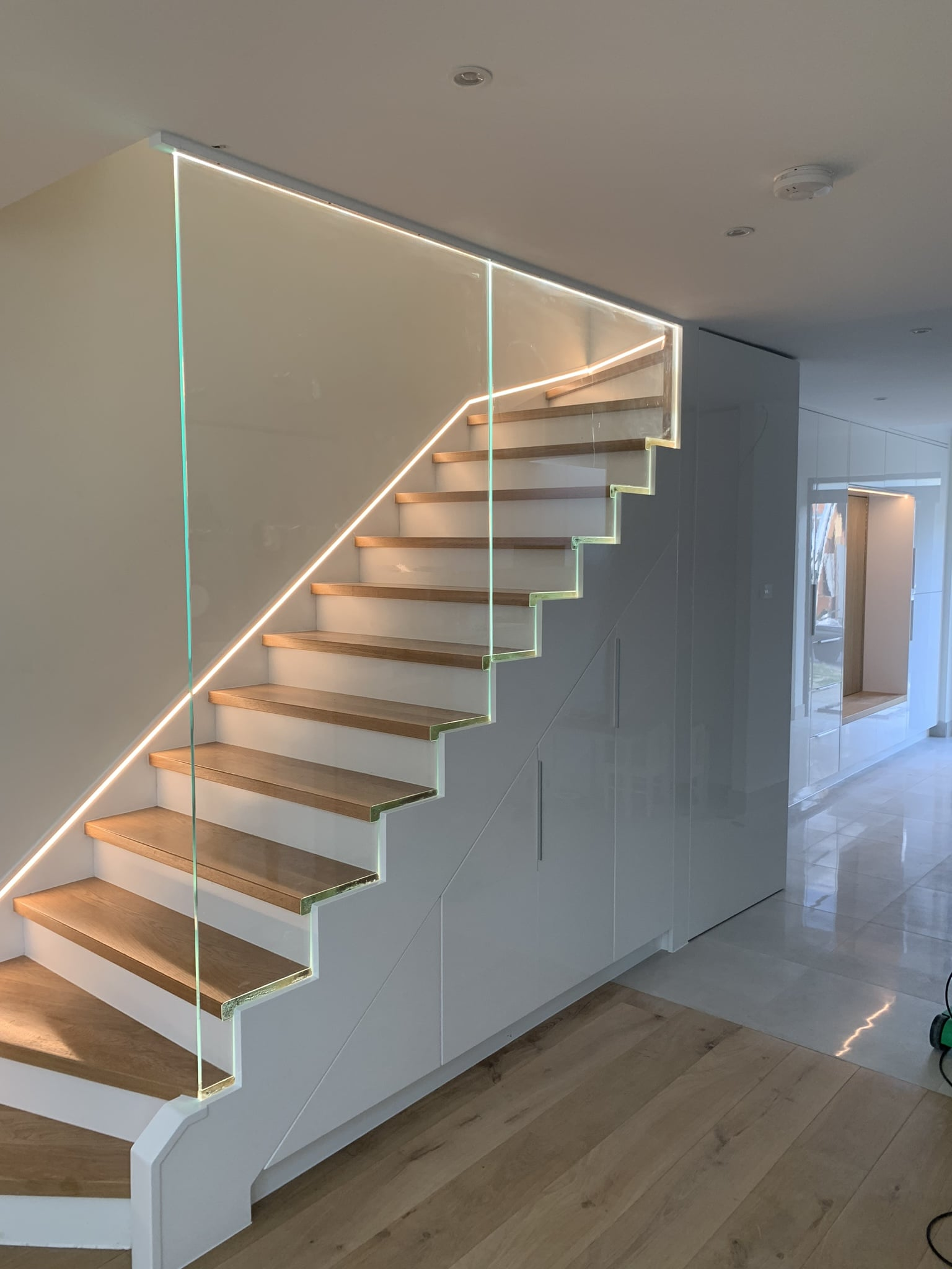Staircase with storage. Safety 12mm glass banister with LED lights.