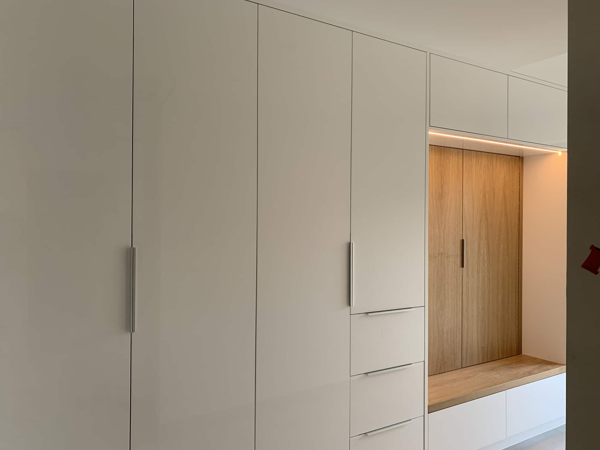 Hallway wardrobe in multi-storage room. Coat hang area with bench. White high gloss finish.