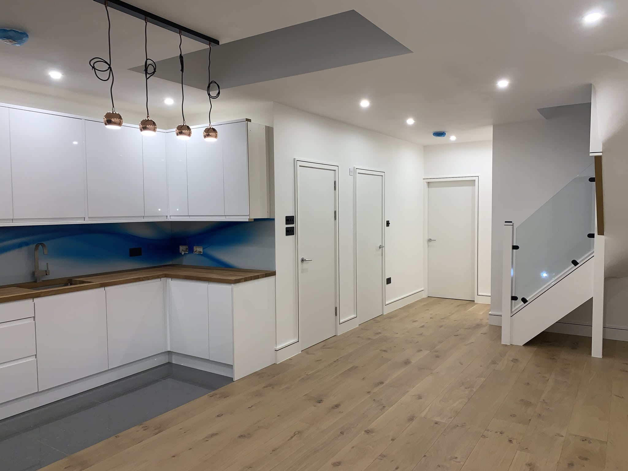 Fitted kitchen with high gloss units and custom glass splashback. Engineered wood floor.