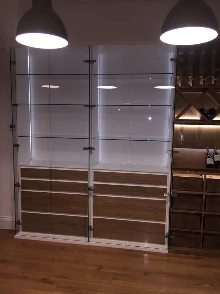 Dining room glass display unit with soft closing drawer and wine storage with hunting bar glass ruck.