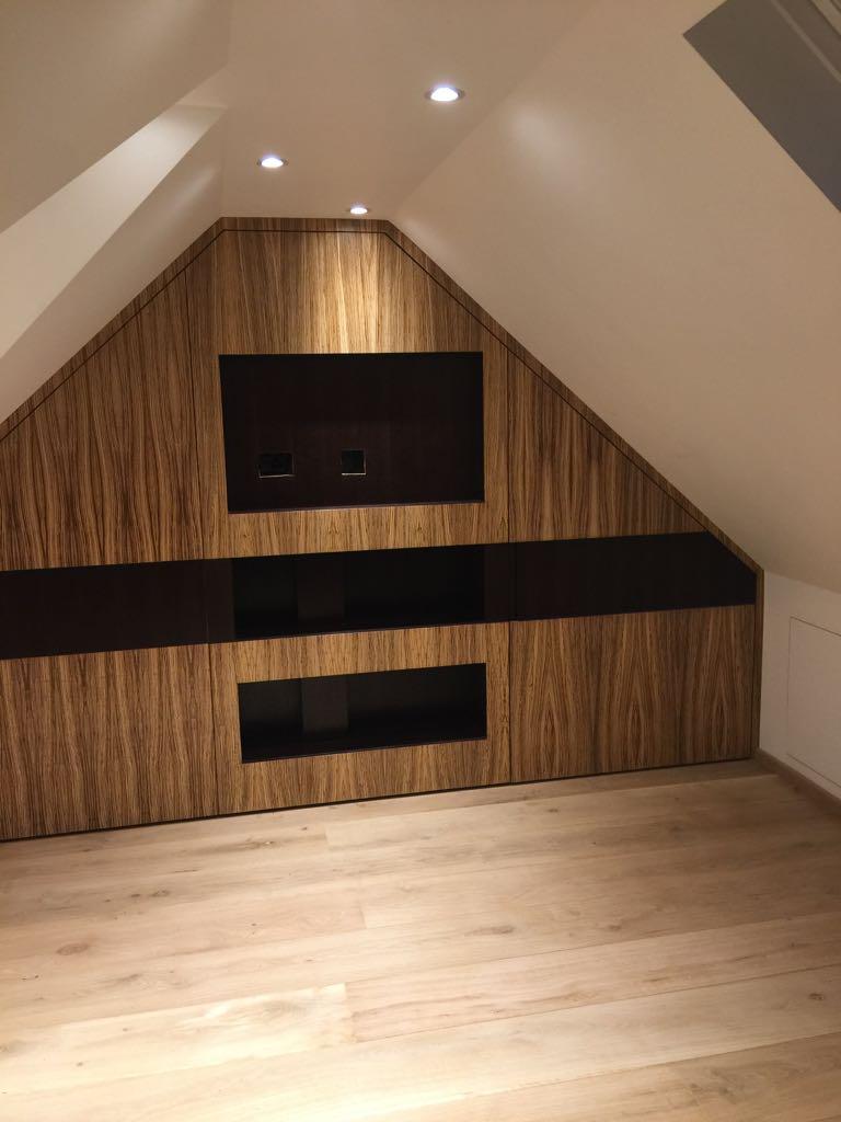Bespoke loft TV unit with storage in Zibrano finish. Engineered wood flooring.