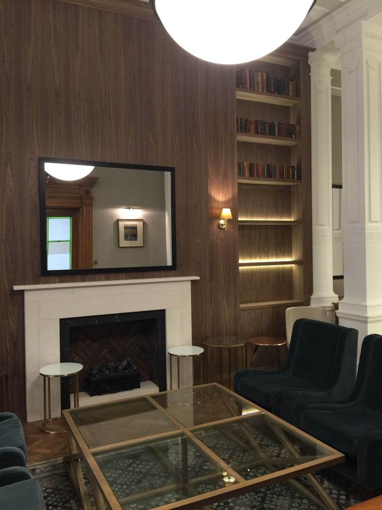 Fireplace with walnut chimney cladding and bookshelves.